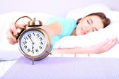 Beautiful young woman sleeping on bed with alarm clock in bedroom — Stock Photo