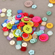Buttons of different shapes, sizes and colors close-up on gray background — Stock Photo