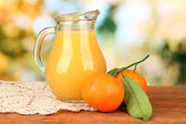 充分 jug 的桔子汁,在明亮的背景上的木桌上 — 图库照片