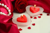 Beautiful candles and rose on red silk background — Stock Photo