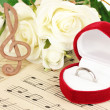 Treble clef, roses and box holding wedding ring on musical background — Стоковая фотография