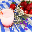 Delicious strawberry yogurt in glass on wooden table close-up - Stock Photo