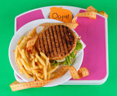 Hamburger, french fries on plate on scale on green background — Stock Photo