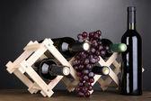 Butelki wina na drewniany stojak na szarym tle — Zdjęcie stockowe