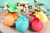 Oeufs de pâques sur plaque avec serviette et fleurs gros plan — Photo