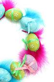 Corona de brillantes huevos de pascua y plumas decorativas, aisladas en blanco — Foto de Stock