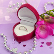 Beautiful box with wedding ring and flower on purple background - Lizenzfreies Foto