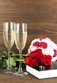 Anéis de casamento na bíblia com rosas e copos de champanhe em fundo de madeira — Foto Stock
