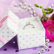 Beautiful box with wedding ring and flower on purple background — Stock Photo