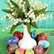 Easter eggs on wooden surface with flowers on turquoise background — Stock Photo #24210415