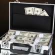 Suitcase with 100 dollar bills isolated on black — Stock Photo