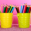 Colorful pencils in two pails on table on pink background — Stock Photo #24211917