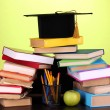 Books and magister cap against school board on wooden table on green background — Lizenzfreies Foto