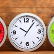 Round office clocks on wooden background — Stock Photo