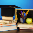 Books and magister cap against school board on wooden table on blue background — Stock Photo