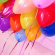 Many bright balloons under ceiling close-up — Stock Photo #24213385