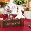 Reserved sign on restaurant table with empty dishes and glasses — Stock Photo #24213411