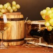 Stock Photo: Wooden case with wine bottle, barrel, wineglass and grape on wooden table on brown background