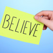 Believe word on piece paper in hand on blue background — Stock Photo