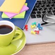 Laptop with stationery and cup of coffee on table — Stock Photo #24214153