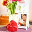 Beautiful tulips in bucket with gifts on table in room — Zdjęcie stockowe