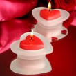 Beautiful candles and rose on red silk background — Stock Photo #24215427