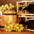 Wooden case with wine bottle, barrel, wineglass and grape on wooden table on brown background — Stock Photo #24215975