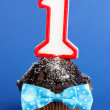 Birthday cupcake with chocolate frosting on blue background — Stock Photo