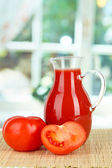 Tomato juice in pitcher on table on in room — Stock Photo