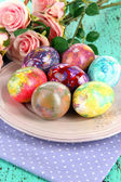 Easter eggs on plate with napkin and flowers close-up — Stockfoto