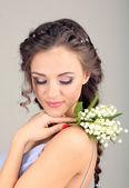 Ung kvinna med vackra frisyr och blommor, på grå bakgrund — Stockfoto