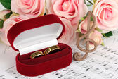 Treble clef, roses and box holding wedding rings on musical background — Stock Photo