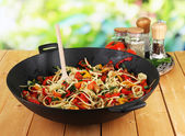 Noodles with vegetables on wok on nature background background — Stock Photo