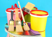 Set for painting: paint pots, brushes, palette of colors on blue background — Stock Photo