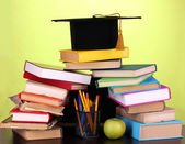 Books and magister cap against school board on wooden table on green background — Stok fotoğraf