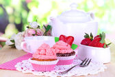 Beautiful strawberry cupcakes and flavored tea on dining table on natural background — Stock Photo