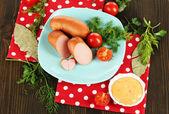 Saucisse, les verts, les tomates sur la plaque sur la table en bois — Photo