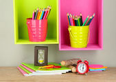 Colorful pencils in pails on shelves on beige background — Стоковое фото