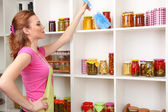 Young housewife cleaning up kitchen on grey background — Stock Photo