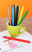 Colorful pencils in cup on table on orange background — Stock Photo