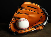 Baseball glove and ball on dark background — Stock Photo