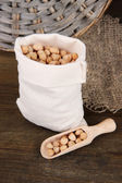 Beans in sack on wooden background — Stock Photo