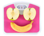 Apple and banana on scales isolated on white — Stock Photo