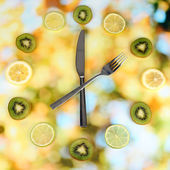 Clock made of kiwi, lime and lemon slices, on bright background — Stock Photo