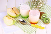 Delicious yogurts with fruits in glasses on wooden table close-up — Stock Photo