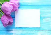 Mooi boeket van paarse tulpen en lege kaart op blauwe houten achtergrond — Stockfoto