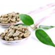 Green coffee beans in wooden spoons and leaves isolated on white — Stock Photo #24274101
