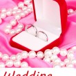 Wedding rings in red box on pink cloth background — Stock Photo #24276965
