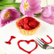 Sweet cake with strawberry and sauce on plate, on wooden background - Stock Photo