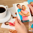 Photos in hands on wooden table — Stock Photo #24277081
